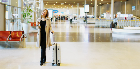 Website banner of young caucasian woman with valise walking in waiting hall at airport. Concept of blog header, heading and cheap tickets for traveling abroad, travel agency and business trips.
