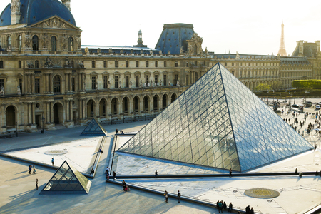 People walking in Louvre near glass pyramid, Paris, France. Concept of traveling and cheap tours to European landmarks.