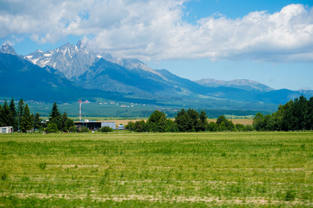 Amazing Tatra Mountains in Slovakia with blue sky background and green grass field. Concept of cheap tours to european resorts for summer vacations in wild nature.