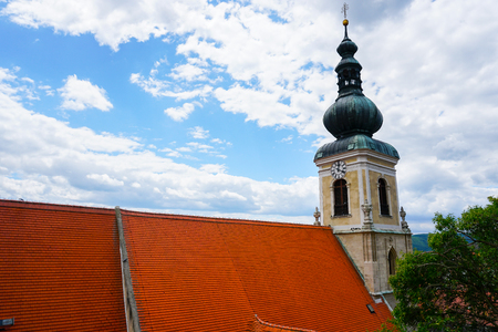 Austrian Christian church with red tiled roof. Concept of european Catholic exterior and religious building, architecture.