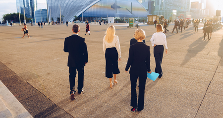 Business team members passing outside in  . Concept of employees of financial organization. People dressed in black suits walking outdoors.