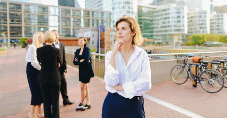Businesswoman looking at camera with close up face in   and speaking employees background. Concept of female boss and successful team work. People in business wear style discussing best decisions outside.