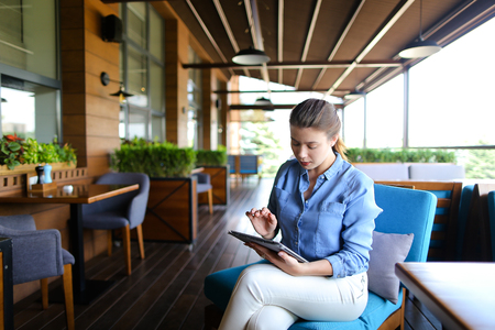 Young girl using tablet at restaurant   and sitting in on blue sofa. Pretty woman wears jeans shirt and has pony tail. Concept of modern gadgets and hotspot Internet.