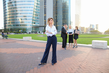Secretary standing in La Defense Paris and looking at camera near speaking employees with boss in background. Concept of successful financial team members talking about best solutions. People dressed in business clothes making decisions with laptop outside.