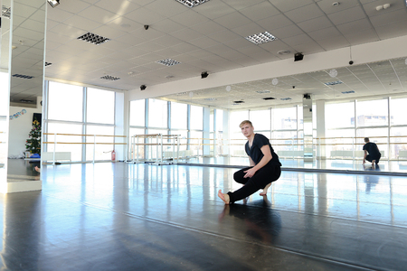 Male athlete making handstand at dancing studio with legs spread out. Young person training in decorated gym. Physical exercises near big mirrors. Stock Photo