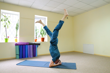 Young brunette of American origin sits on yoga mat and performs longitudinal twine. Short-haired sportswoman dressed in blue sports pants and blue t-shirt. Room light and spacious, under wall multi-colored yoga mats. Concept of to maintain body in good physical shape, in care of health.