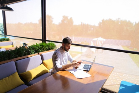 Real estate agent speaking with client on smartphone and working with laptop at table with papers. Prosperous man dressed in white shirt has dark hair, beard and watch. Concept of buying, selling or renting properties on behalf customers and using advantageous tariff plan for long talks.