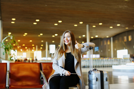 Caucasian nice girl sitting at airport hall with tablet and valise, showing thumbs up. Concept of traveling and modern technology.