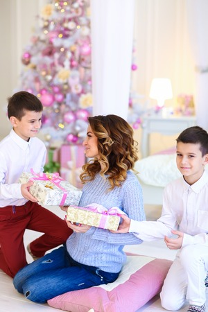 Two caucasian sons gifted present for mother near decorated fir tree. Concept of christmas tipme and winter holidays, happy family.