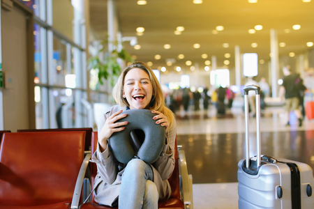 Young woman sitting at airport waiting hall with neck pillow and valise. Concept of traveling.