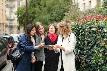 Female students speaking with curator and showing photos on tablet outdoors in .
