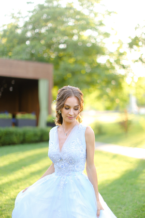 Happy pretty fiancee standing in park. oncapt of bridal hair do and wedding photo session on nature.