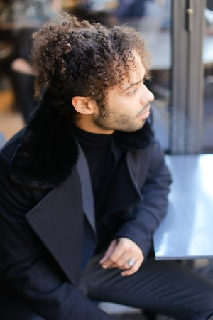Afro american man with curly hair wearing black coat. Concept of young male person. 스톡 콘텐츠