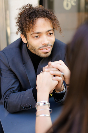 Focus on afro american handsome boy holding female hands and sitting at street cafe. Concept of love and dating with black man.