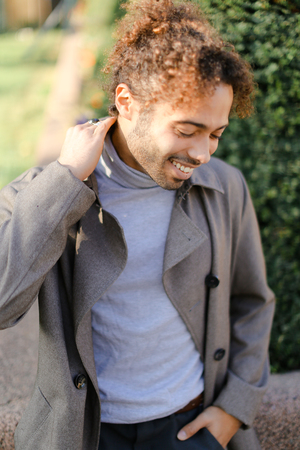 Afro american young boy with curly hair smiling and standing outside. Concept of black male person.