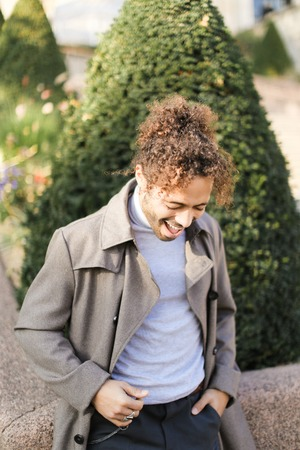 Afro american boy with curly hair smiling and standing outside. Concept of black male person.