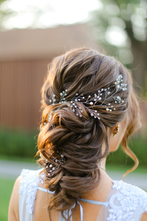 Back view portrait of amazing fiancee outside. Concept of bridal hair do and wedding style.