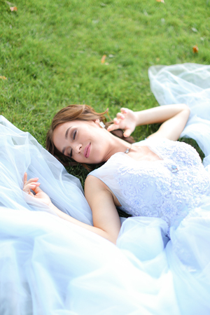Innocent smiling fiancee lying on grass in oark and wearing white dress. Concept of beauty and bridal photo session in open air.