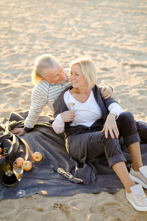 Senior caucasian husband hugging wife sitting on plaid with champagne on sand beach. Concept of elderly couple on picnic. Фото со стока