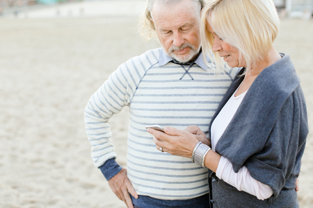 Elderly couple using internet by smartphone on sand beach. Concept of pensioners and modern technology.