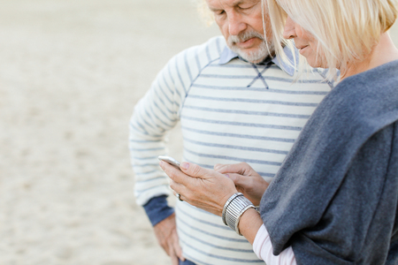 Elderly couple browsing by smartphone on sand beach. Concept of pensioners and modern technology.