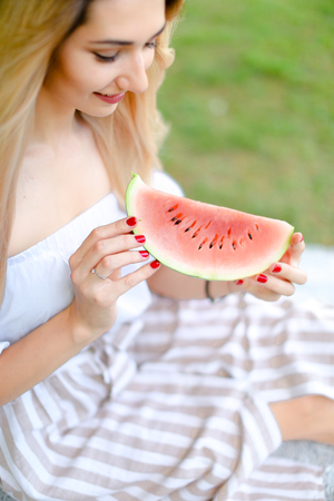 Young caucasian girl eating watermelon and wearing dress, grass in background. Concept of summer photo session, picnic.