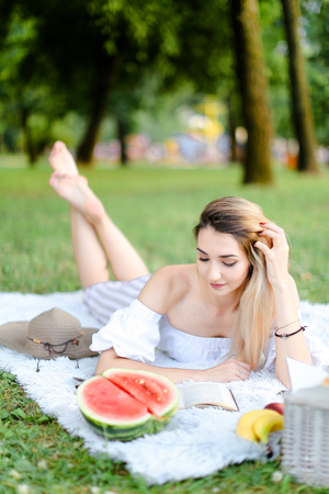 Young european girl lying on plaid in park near watermelon and reaing book. Concept of picnic and resting in open air on weekends. Stock Photo