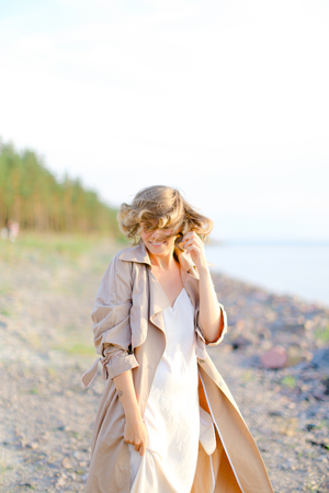 Young smiling woman standing on sea beach and wearing coat with white dress. Concept of enjoying freedom and summer photo session.