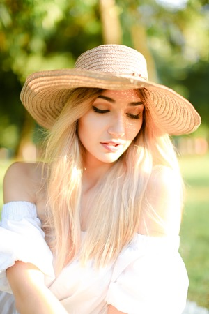 Portrait of young blonde caucasian girl in hat. Concept of beauty, female person and summer fashion.