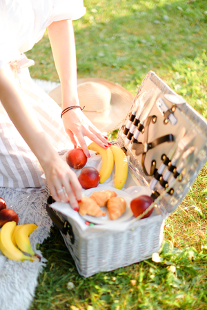 Female hands put fruits into box, grass in background. Concept of summer picnic and vegeterian lifestyle.