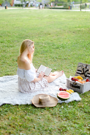 Young girl reading book and sitting on plaid near fruits in park. Concept of having summer picnic and leisure time.