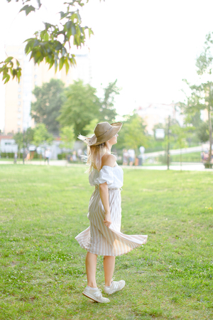 Back view of young girl wearing hat and dress, standing in park on grass. Concept of summer season fashion and female person. Фото со стока