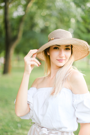 Portrait of young pretty caucasian girl wearing hat and smiling. Concept of beauty, female person and summer fashion.