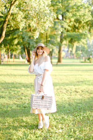 Young blonde woman wearing hat and dress standing in garden with bag. Concept of beautiful female person, summer fashion and walking in park.