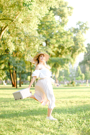 Young caucasian woman jumping in park and running, wearing fashionable clothes and hat. Concept of summer sales and style.