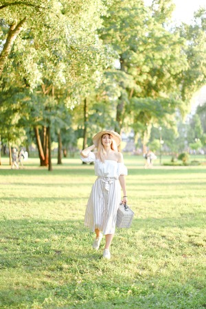 Young nice girl walking in garden and keeping bag, sunglasses and hat. Concept of walking in park and summer fashion. Фото со стока