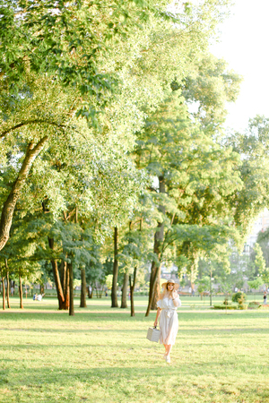 Young girl wearing hat walking in garden with bag in sunny day. Concept of summer season, fashion and female person walking in park. Фото со стока