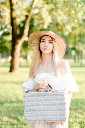 Young charming woman wearing hat and dress standing in garden with bag. Concept of beautiful female person, summer fashion and walking in park.