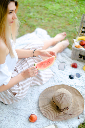 Young blonde woman sitting on plaid near fruits and hat, eating watermelon, grass in background. Concept of summer picnic and resting on weekends in open air. Banco de Imagens
