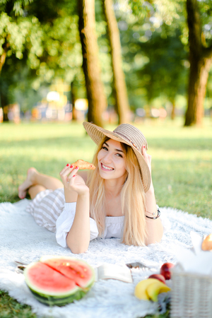 Young blonde girl in hat with croissant lying in park on plaid near watermelon. Concept of having free time, picnic and bakery products.