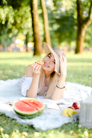 Young happy blonde woman in hat with croissant lying in park on plaid near waterlemon. Concept of having free time, picnic and bakery products.
