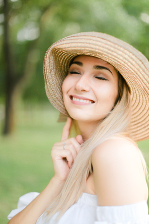 Portrait of young cute caucasian girl wearing hat and smiling. Concept of beauty, female person and summer fashion.