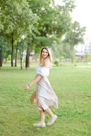 Young caucasian girl wearing dress, standing in park and keeping hat. Concept of summer season and fashion.