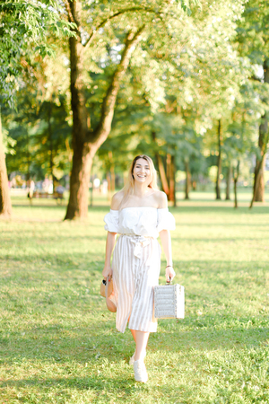 Young caucasian girl walking in garden and keeping bag, sunglasses and hat. Concept of walking in park and summer fashion. Фото со стока