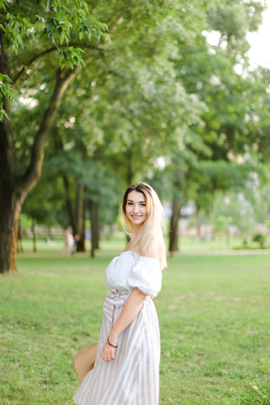 Young pretty girl wearing dress, standing in park and keeping hat. Concept of summer season and fashion.