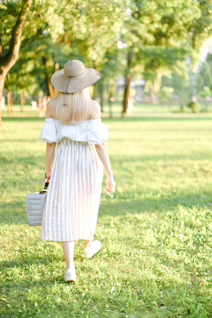 Back view of young pretty girl in hat walking in garden and keeping bag. Concept of walking in park and summer fashion garb. Фото со стока
