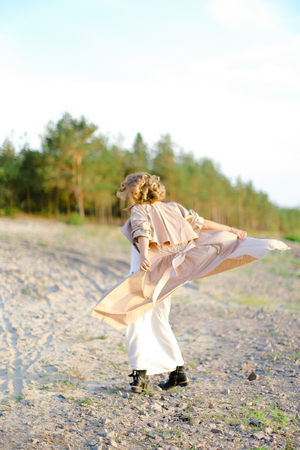 Young woman turning around on sand and wearing coat with white dress. Concept of happiness, summer vacations and fashion. Фото со стока