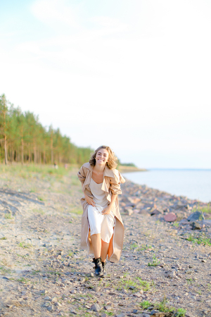 Smiling blonde woman wearing coat and white dress standing on sand with trees in background. Concept of happiness, youth and fashion, summer vacations.