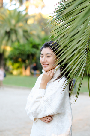 Chinese beautiful woman in white sweater standing near palm leaf. Concept of asian beauty and female person on tropical resort. Фото со стока