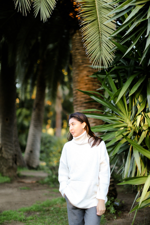 Chinese girl walking in tropical park and standing near palms. Concept asian beauty and nature.